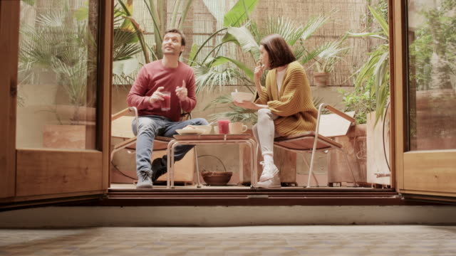 stockvideo's en b-roll-footage met paar praten tijdens het ontbijten in de tuin - meubels