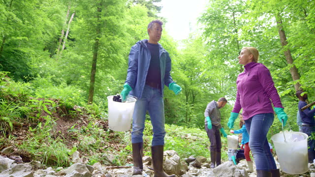 couple talking while picking up litter in the local forest and helping in the local cleanup - littering stock videos & royalty-free footage