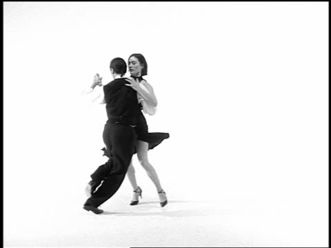 b/w overexposed couple tango dancing on white surface in studio / slow motion at end of shot - tango dance stock videos & royalty-free footage