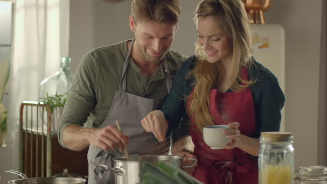 stockvideo's en b-roll-footage met couple tasting self-made food in the kitchen - proeven