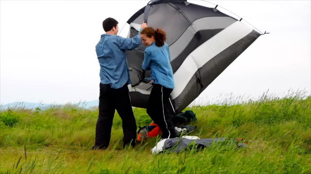 stockvideo's en b-roll-footage met couple tent camping on mountain top - tent