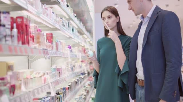 vídeos de stock e filmes b-roll de couple testing perfumes by perfume counter - perfumado
