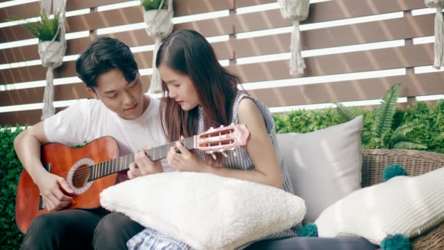 couple thai university students trying to play guitar with love emotion - chord stock videos and b-roll footage
