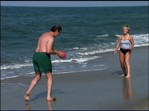 couple throwing football on beach - 50 59 years stock videos & royalty-free footage