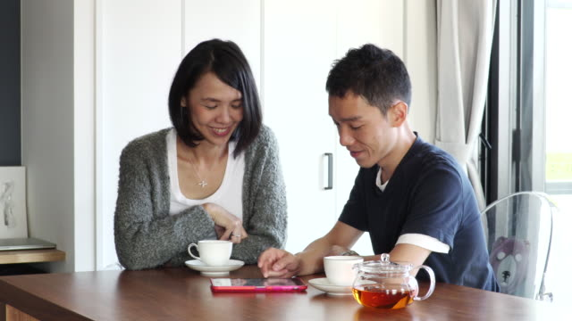 couple to talk while watching the tablet - tea cup stock videos & royalty-free footage