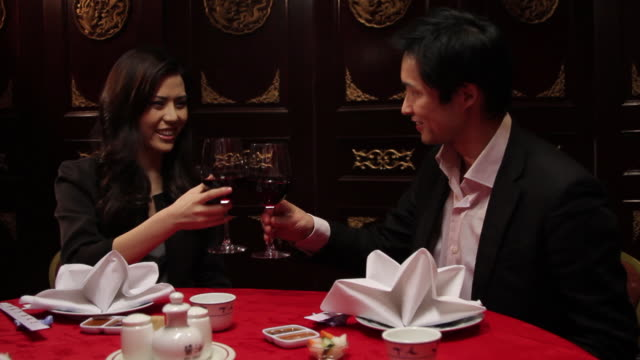 couple toasting in chinese restaurant - 恋に落ちる点の映像素材/bロール