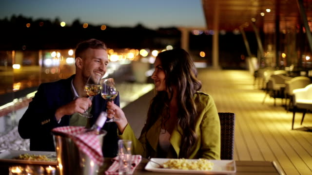 Couple toasting with white wine in restaurant