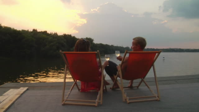 SLO MO WS Couple toasting with wine while sitting on deck chairs overlooking lake at sunset / Potsdam, Germany