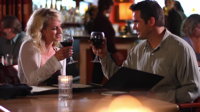 A couple toasts with wine at a restaurant.
