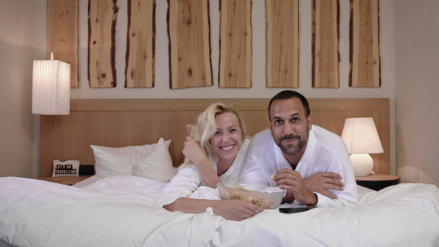 couple together in hotel room watching TV movie - she in her 30s with long blonde hair he in his 30s with short dark hair and trimmed beard both wearing bathrobe gown while lying on king size bed and looking into telly tube - snacking crackers out of bowl