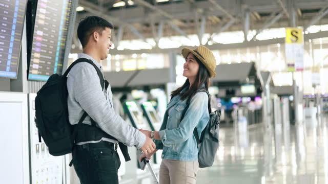 stockvideo's en b-roll-footage met de reizigers van het paar met medische maskers bij de luchthaven, vakantievakantie - voetgangerspad
