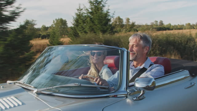 vídeos de stock e filmes b-roll de couple traveling in classic car during windy day - homens adultos
