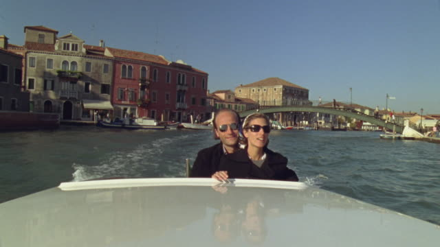 WS Couple traveling in water taxi on canal near bridge and waterfront / Venice, Italy