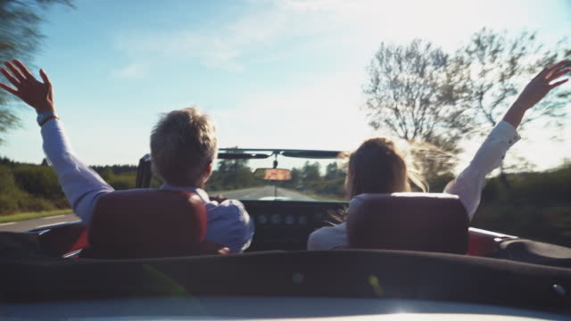 couple traveling with raised hands in vintage car - human age stock videos & royalty-free footage