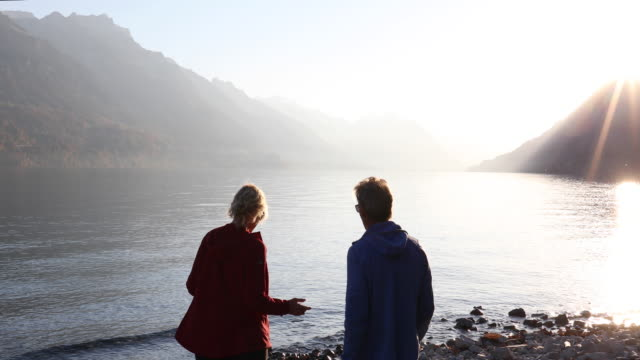 Couple traverse lakeshore, take pic down lake