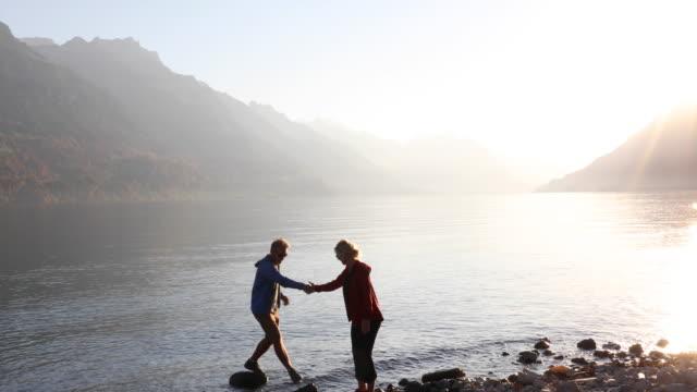 Couple traverse lakeshore, woman provides assistance