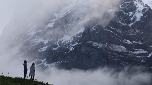 Paar traverse weide onder torenhoge besneeuwde toppen