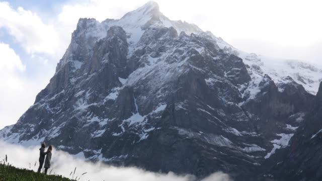 Paar durchqueren Wiese unter hohen schneebedeckten Gipfeln