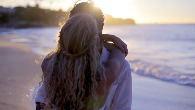 Couple turning and kissing during the sunset at the beach