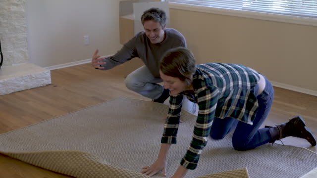 couple unrolling rug on floor in living room, close up. - rug stock videos & royalty-free footage