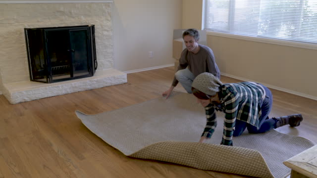 couple unrolling rug on floor in living room. - ラグ点の映像素材/bロール