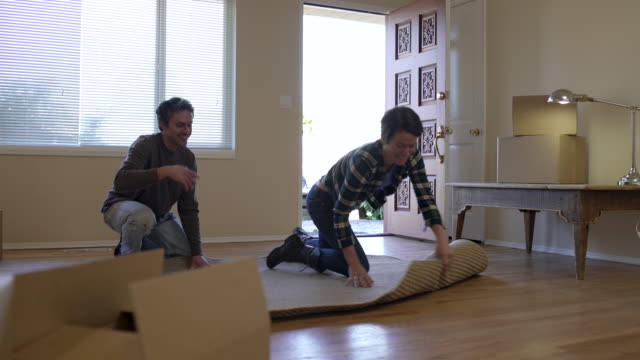 couple unrolling rug on living room floor. - ラグ点の映像素材/bロール