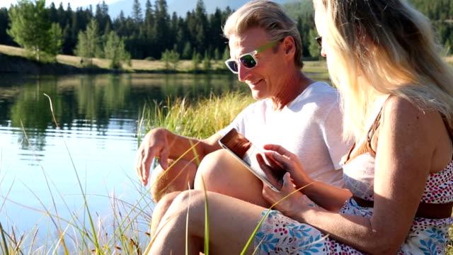 Couple use digital tablet on lakeshore