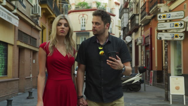 couple using cell phone to navigate direction in city / seville, sevilla, spain - ecke eines objekts stock-videos und b-roll-filmmaterial