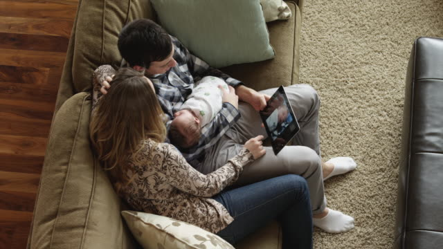 vídeos de stock, filmes e b-roll de ha ms couple using digital tablet, sitting with baby son (0-1 months) on sofa / lehi, utah, usa - lehi