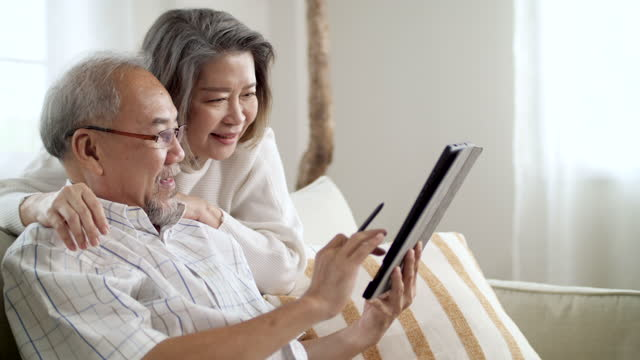 couple using digital tablet together at cozy home - mature couple stock videos & royalty-free footage