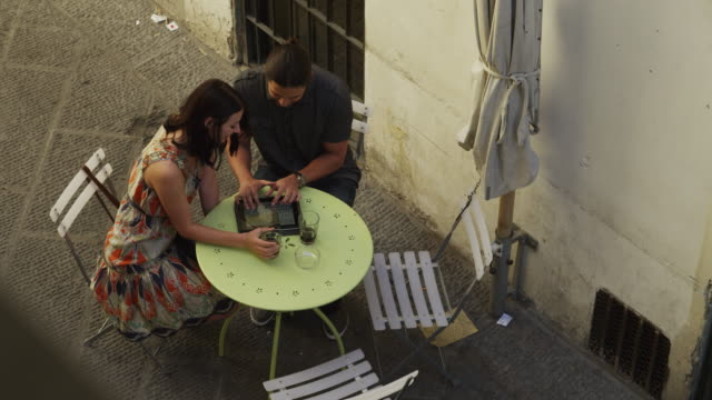 ws ha couple using digital tablet,sitting in outdoor table / florence,tuscany - newoutdoors stock videos & royalty-free footage