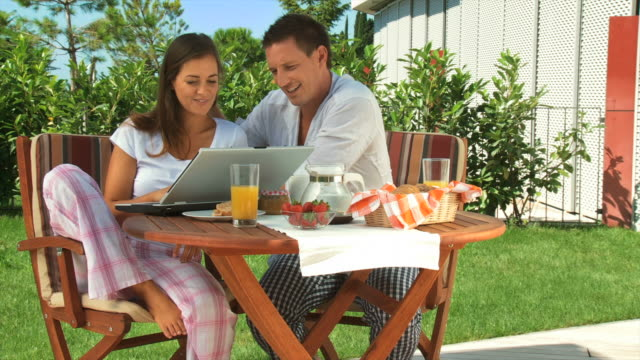 hd dolly: couple using laptop after breakfast - nightwear stock videos & royalty-free footage