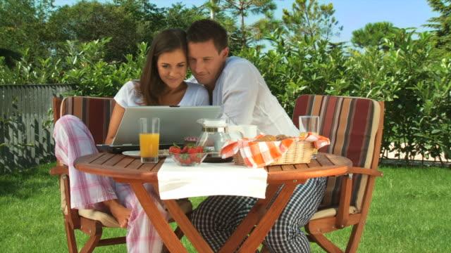 hd dolly: paar mit laptop nach dem frühstück - terrasse grundstück stock-videos und b-roll-filmmaterial