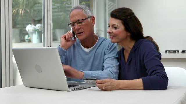 stockvideo's en b-roll-footage met couple using laptop, man on phone woman holding credit card - draadloze telefoon