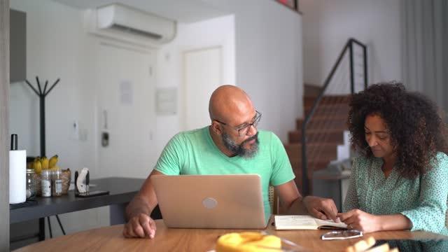 par som använder bärbar dator för att betala räkningar eller handla hemma - savings bildbanksvideor och videomaterial från bakom kulisserna