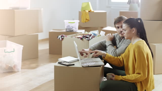 Couple using laptop together at their apartment full of unpacked boxes