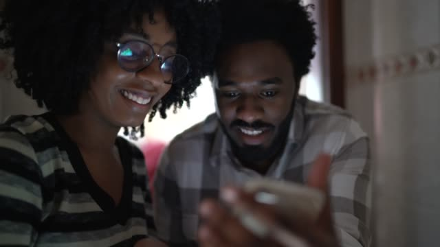 couple using mobile phone at home - facial expression stock videos & royalty-free footage