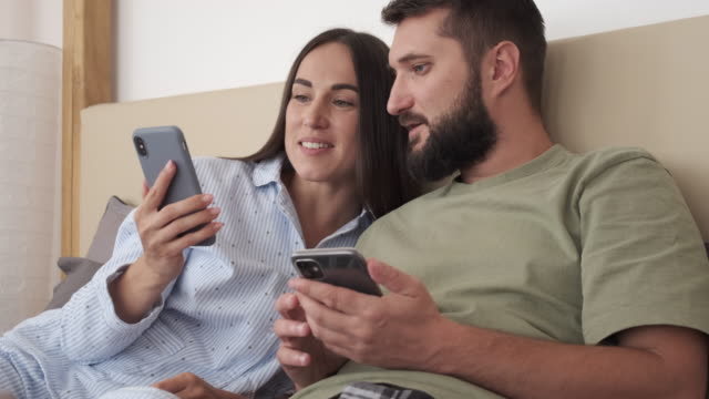 vídeos y material grabado en eventos de stock de pareja usando teléfonos móviles en la cama - pareja joven