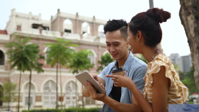 couple using tablet by the sultan abdul samad building - sultan abdul samad building stock videos & royalty-free footage