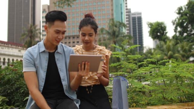 vídeos de stock e filmes b-roll de couple using tablet in the public park - edifício do sultão abdul samad