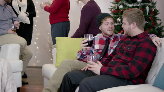 4k uhd: couple visiting on a couch at a lgbtq holiday party - intersex stock videos and b-roll footage