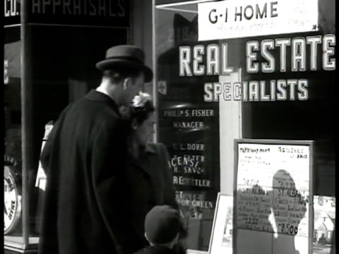 stockvideo's en b-roll-footage met couple w/ child walking up to real estate office window handwritten ads in window parkway manor bungalw [sic] $10750 st alban's $8500 - 1946