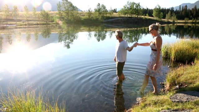 Couple wade into mountain lake at sunrise