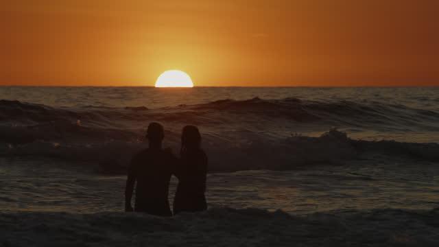 couple wading in ocean waves admiring sunset / san blas, la libertad, el salvador - walking in water stock videos & royalty-free footage