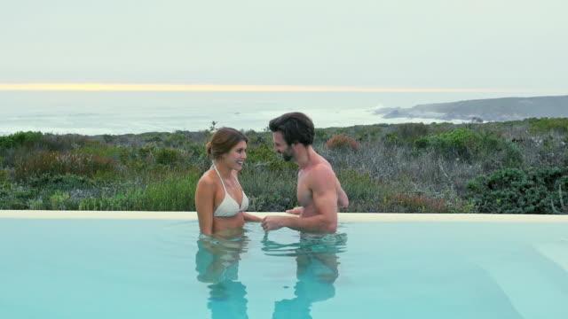 vídeos de stock, filmes e b-roll de couple wading in pool - lago infinito