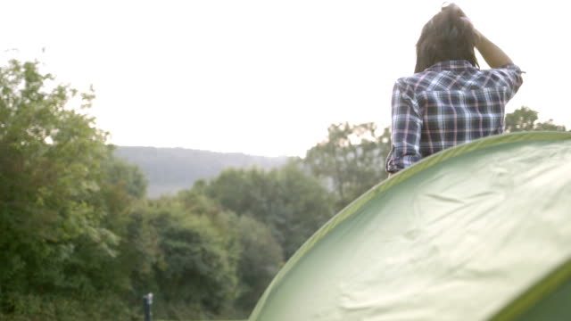 Couple waking up and getting out from dome tent at morning