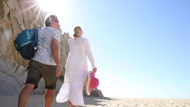 couple walk across sandy beach below cliffs, sunshine - zaino da montagna video stock e b–roll