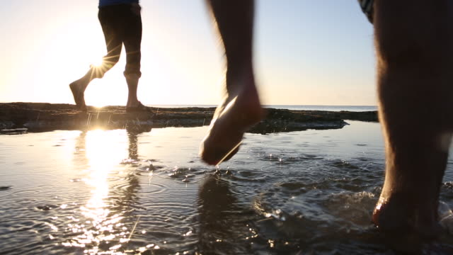 Couple walk across tidal pools, rising sun behind