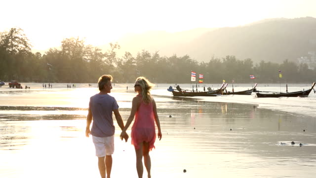 Couple walk along beach at sunrise, tidal flat