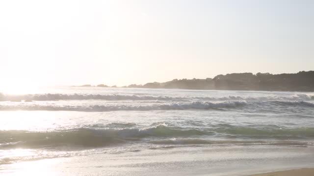 couple walk along beach nears surf edge, sunset - pacific ocean stock videos & royalty-free footage